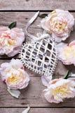 El corazón decorativo y las peonías rosadas florece en backgr de madera envejecido imagenes de archivo