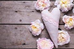 El corazón decorativo y las peonías rosadas florece en backgr de madera envejecido foto de archivo