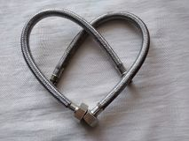 El corazón del fontanero se hace de las mangueras del agua para un fregadero, una trenza del metal del color de acero, el día de  imágenes de archivo libres de regalías