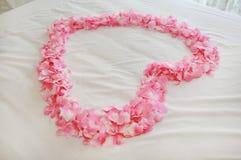 El corazón del rosa artificial subió los pétalos en una cama honeymoon imágenes de archivo libres de regalías