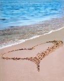 El corazón en la arena de la playa imagenes de archivo