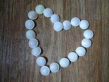 El corazón hizo del caramelo en piso de madera fotografía de archivo libre de regalías
