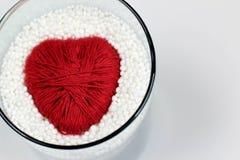 El corazón hizo el hilado de lanas, protegido por las pelotillas ampliadas del poliestireno fotografía de archivo libre de regalías