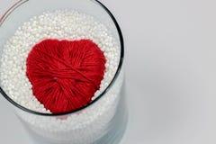 El corazón hizo el hilado de lanas, protegido por las pelotillas ampliadas del poliestireno fotos de archivo libres de regalías