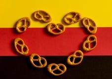 El corazón puso la silueta de muchos pequeños pretzeles en un fondo de los colores alemanes de la bandera Imagen de archivo libre de regalías