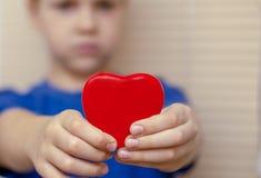El corazón rojo, estira al muchacho adelante con sus manos imagen de archivo libre de regalías