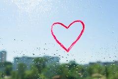 El corazón rojo pintado con el lápiz labial en la ventana con agua cae El cielo soleado azul del fondo, descensos brilla en el so Foto de archivo libre de regalías
