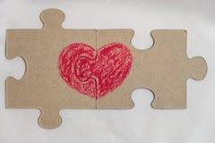 El corazón rojo se dibuja en las piezas del rompecabezas que mienten uno al lado del otro Imagen de archivo