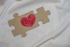El corazón rojo se dibuja en las piezas del rompecabezas que mienten uno al lado del otro Foto de archivo