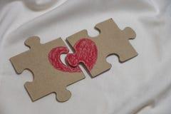 El corazón rojo se dibuja en pedazos de un rompecabezas que miente en una distancia Foto de archivo libre de regalías