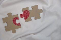 El corazón rojo se dibuja en pedazos de un rompecabezas que miente en una distancia Imagenes de archivo
