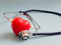 El corazón rojo usando el estetoscopio azul profundo en el fondo azul para oye su propio corazón Concepto de amor y de paciente q imagen de archivo libre de regalías