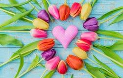 El corazón rosado del amor con los tulipanes coloridos florece para el día del ` s de la tarjeta del día de San Valentín o del `  Foto de archivo