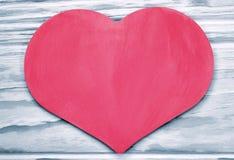 El corazón rosado en el fondo teñió tablones de madera Imagenes de archivo
