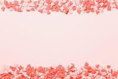 El corazón rosado y rojo asperja en el fondo rosado Endecha plana, visión superior Fondo de las tarjetas del día de San Valentín  foto de archivo