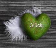 El corazón verde con el texto alemán para la suerte y una pluma blanca encendido cortejan fotografía de archivo libre de regalías