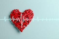 El corazón y el cardiograma trenzados rojos alinean en la tabla azul Imagen de archivo