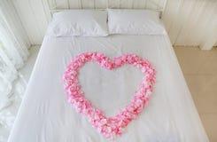 El coraz?n del rosa artificial subi? los p?talos en una cama honeymoon imagen de archivo