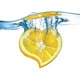 El corazón del limón cayó en el agua Imagen de archivo libre de regalías