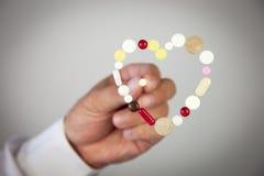 El corazón se hace de las píldoras y de la mano que sostienen una píldora Fotografía de archivo