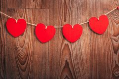 El cordón natural de los corazones del ` s de la tarjeta del día de San Valentín del amor de la guinga y los clips rojos que cuel Fotografía de archivo