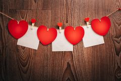 El cordón natural de los corazones del ` s de la tarjeta del día de San Valentín del amor de la guinga y los clips rojos que cuel Imagen de archivo