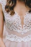 El cordón suave hermoso en el corsé de un vestido beige de la boda elegante adornó con las gotas y el bordado en la novia Foto de archivo libre de regalías