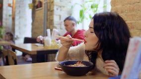 El coreano hermoso con los labios rojos goza de los tallarines de arroz en restaurante coreano almacen de metraje de vídeo