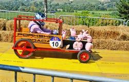 El corredor conduce un coche de carreras diy con los cerdos del juguete abajo de la pista Imagen de archivo libre de regalías