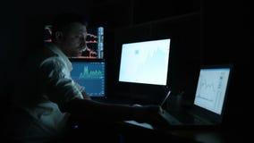 El corredor de bolsa en la camisa blanca está trabajando en un cuarto de supervisión oscuro con las pantallas de visualización Di almacen de metraje de vídeo