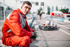 El corredor de Karting se sienta en un neumático, kart en fondo Imagenes de archivo