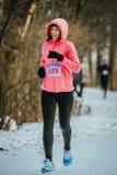 El corredor de la chica joven corre en el parque del invierno en nieve Fotografía de archivo
