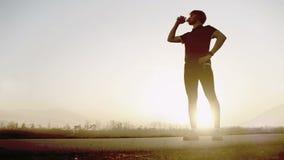 El corredor de maratón bebe el agua en el paisaje granangular de la montaña almacen de video