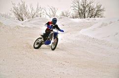 El corredor del motocrós del invierno en una motocicleta da vuelta con la cuesta y Fotografía de archivo