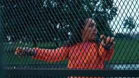 El corredor femenino de la raza mixta joven toma un breve descanso cerca de la pared de la malla en un día lluvioso metrajes