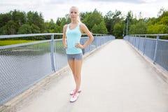 El corredor femenino joven hermoso y confiado se coloca en el puente Foto de archivo libre de regalías