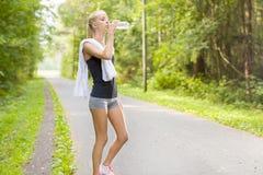 El corredor femenino joven toma una rotura y bebe el agua Fotografía de archivo libre de regalías