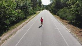 El corredor femenino juguetón hermoso en auriculares y camisa rosada está entrenando en parque de la ciudad La mujer caucásica mo almacen de metraje de vídeo
