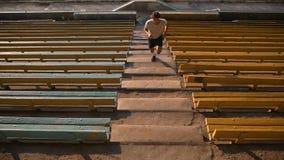 El corredor joven del hombre de la raza mixta en deporte viste el funcionamiento que sube para arriba las escaleras en el estadio almacen de video