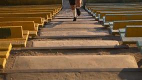 El corredor joven del hombre de la raza mixta en deporte viste el funcionamiento que sube para arriba las escaleras en el estadio metrajes
