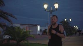 El corredor masculino cansado es que activa y de detención en parque de la ciudad por la tarde, descansando almacen de metraje de vídeo