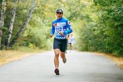 El corredor masculino joven que corre en el parque del otoño, amarillo se va en la tierra Foto de archivo