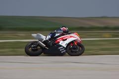 El corredor solo de la moto en el izquierda curva encendido la pista Fotos de archivo libres de regalías