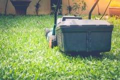 El cortacésped está funcionando en hierba verde en el jardín al aire libre con el fondo de la luz del sol foto de archivo libre de regalías