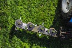 El cortac?spedes montado del disco para el tractor durante trabajo agr?cola, siega la hierba verde jugosa del c?sped durante la r foto de archivo