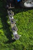 El cortac?spedes montado del disco para el tractor durante trabajo agr?cola, siega la hierba verde jugosa del c?sped durante la r imagen de archivo