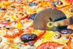 El cortador corta una pizza fotos de archivo