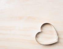 El cortador de la galleta del corazón cuece la herramienta en el fondo de madera blanco, visión superior imagen de archivo libre de regalías