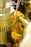 El cortador regula el metal y el aceite fluye de los registros para refrescarse y la lubricación La industria de la metalurgia co fotografía de archivo libre de regalías