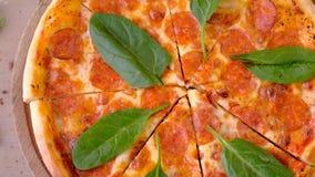 El cortar de la pizza del salami con las hojas de la espinaca en el tablero de madera, opini?n superior del primer almacen de metraje de vídeo